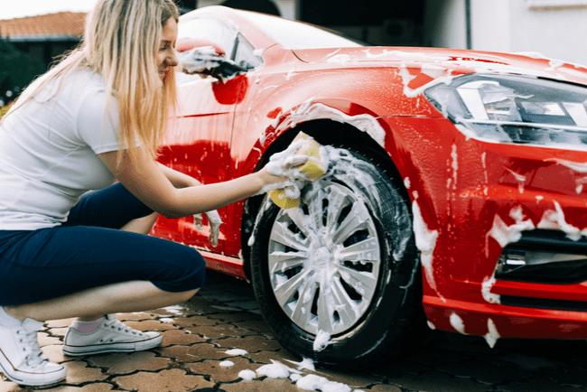 En bild på en kvinna som tvättar bilen