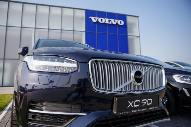 Fronten på Volvo XC90 som strå framför en Volvofabrik.