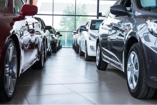 Bilar som står på rad efter varandra i en bilhall.