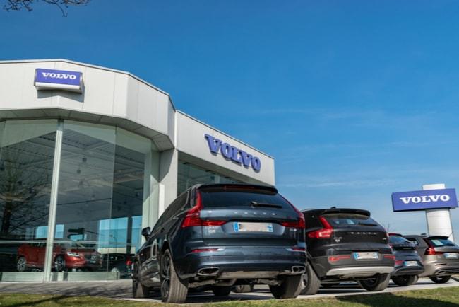 Volvobilar av olika modeller står parkerade utanför en Volvobutik.