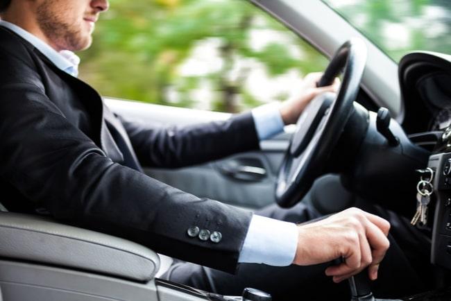 man sitter bakom ratt i bil med handen på växelspaken