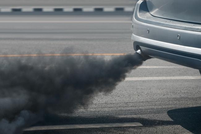 Mörka avgaser som kommer ur avgasröret på en bil.