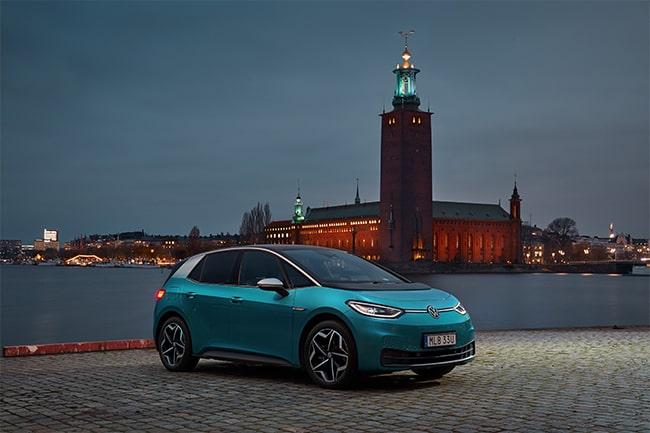 blå elbil står vid kajkant med stadsvy i bakgrunden