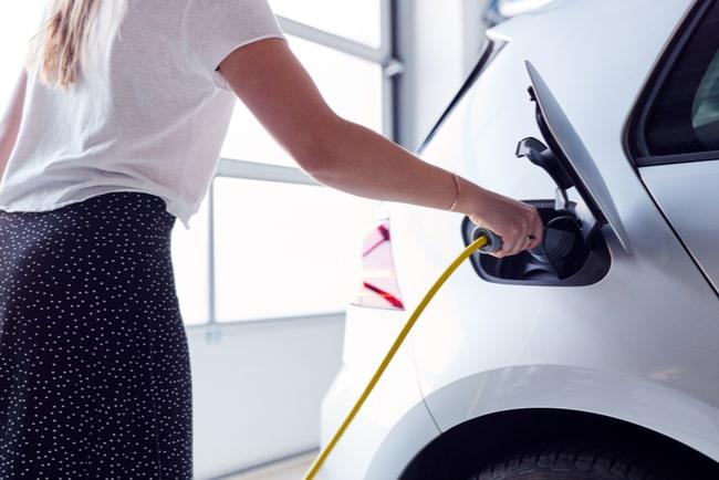 kvinna laddar vit elbil
